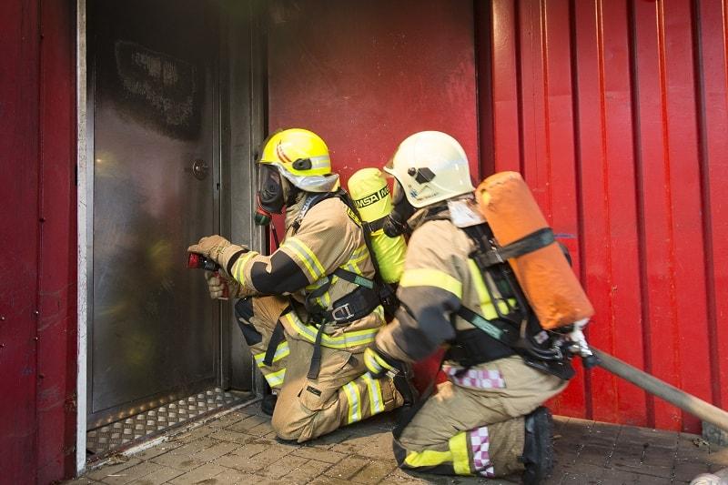 """Zugang zur Brandübungsanlage: Ein Trupp unter Atemschutz an der """"Hot Door""""."""